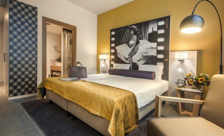 chambre de luxe, peinture jaune, lit deux places, lampadaire design