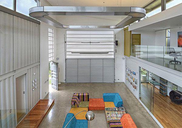 コスタリカ在住のカメラマンがオーナーの家は、8つのコンテナを組み合わせ作ったユニークなお宅。吹き抜けのリビングルームには、大きなガレージドアが付いており、そのまま駐車場に直結するかたちとなっています。 敷地の中央にある、 …
