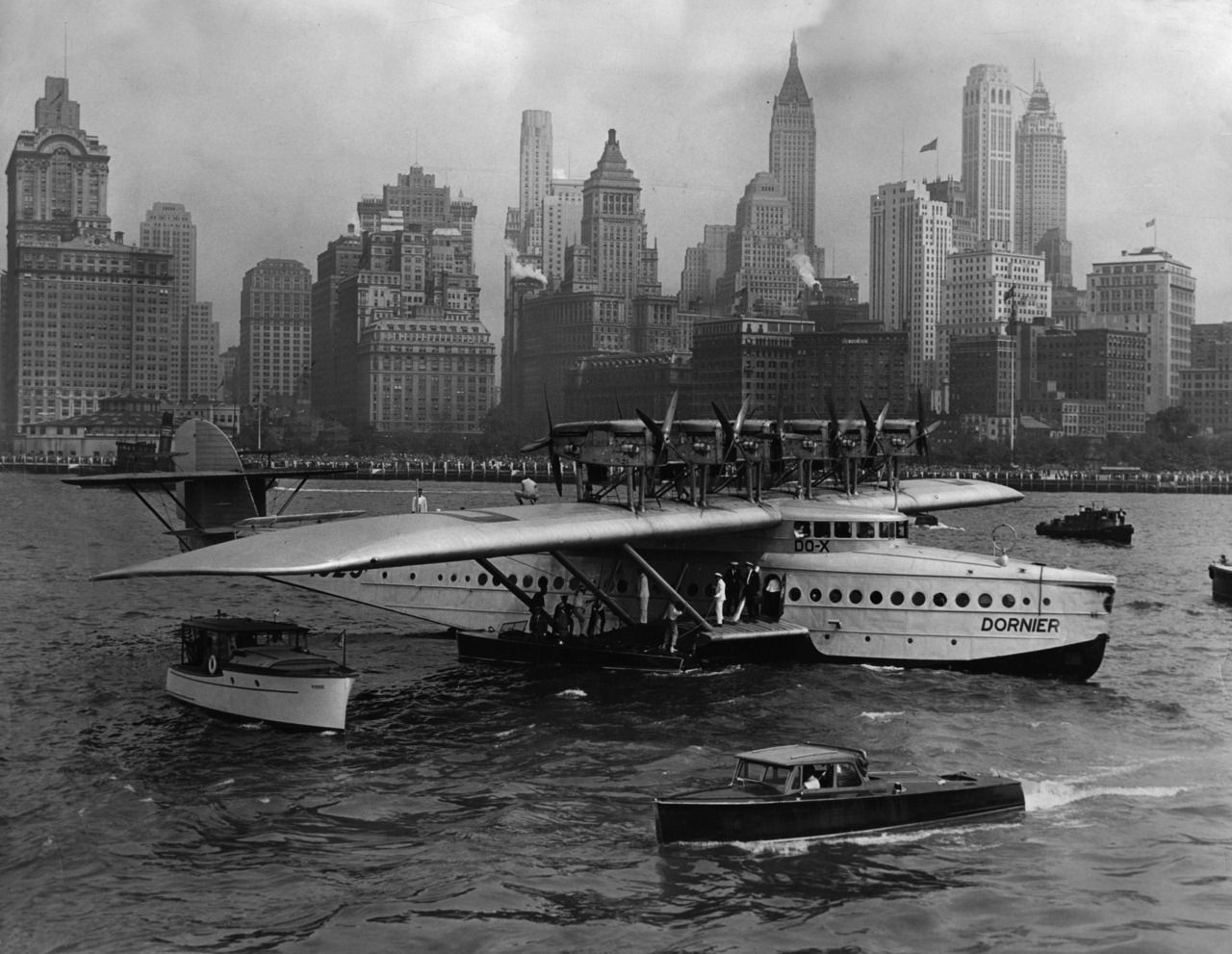 The Dornier Do X seaplane with the registration number D-1929 undertook a demonstration flight from Amsterdam to New York in 1930/31. Passengers board the airplane from a boat which has docked on the starboard small wing.