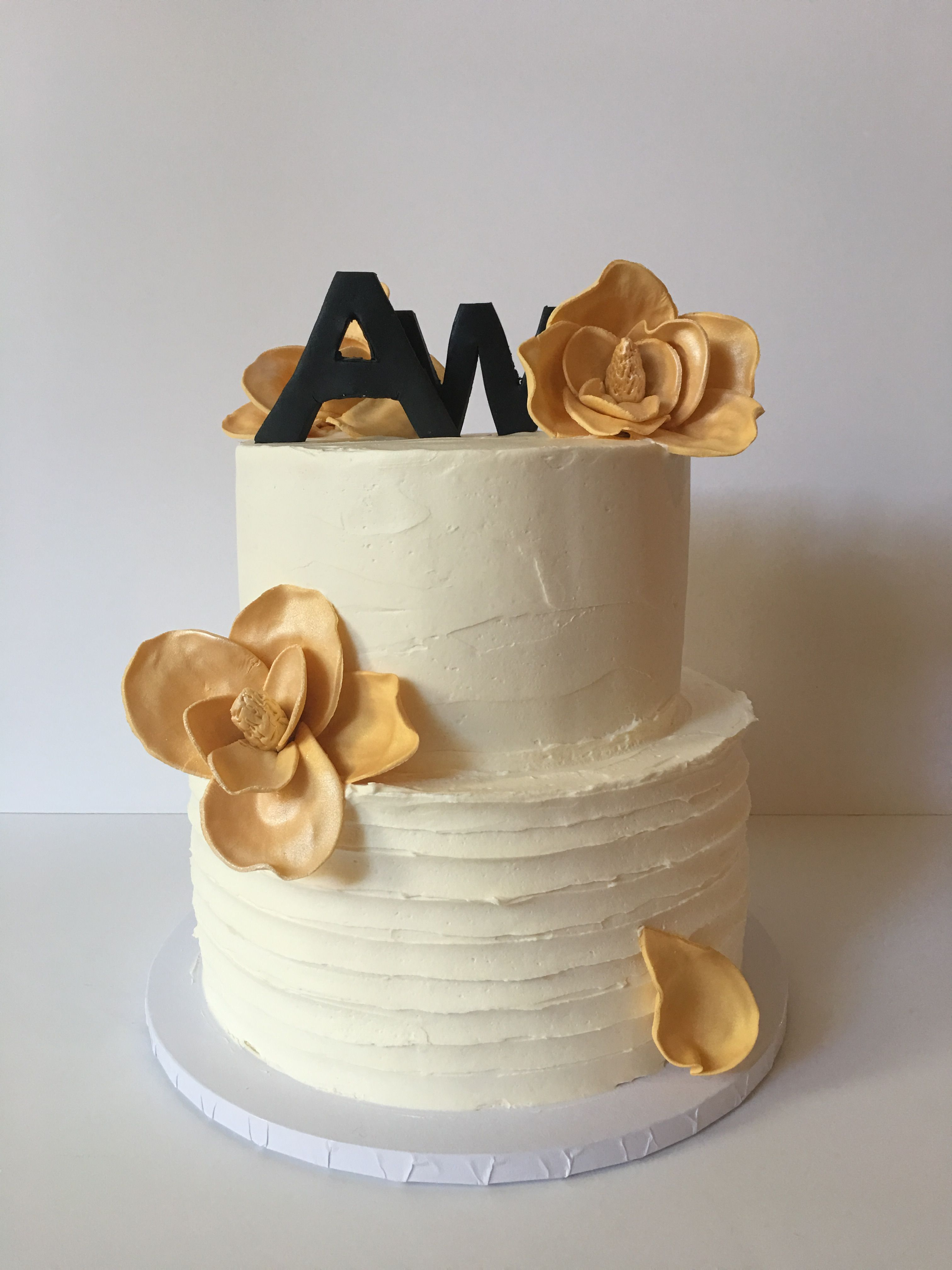 40th birthday party with buttercream finish, initials, and gilded magnolias.