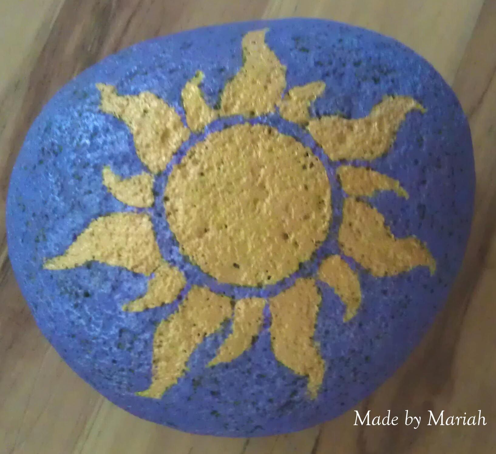 """The sun from """"Tangled"""" painted on to a rock for a door stop"""