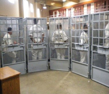 Prisoners in cages await group therapy, Mule Creek State
