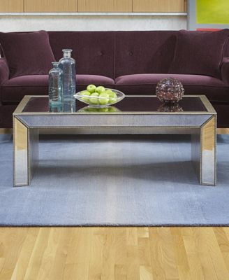 Try using a glass end or cocktail table, staying away from large wood furniture will lighten up the space.
