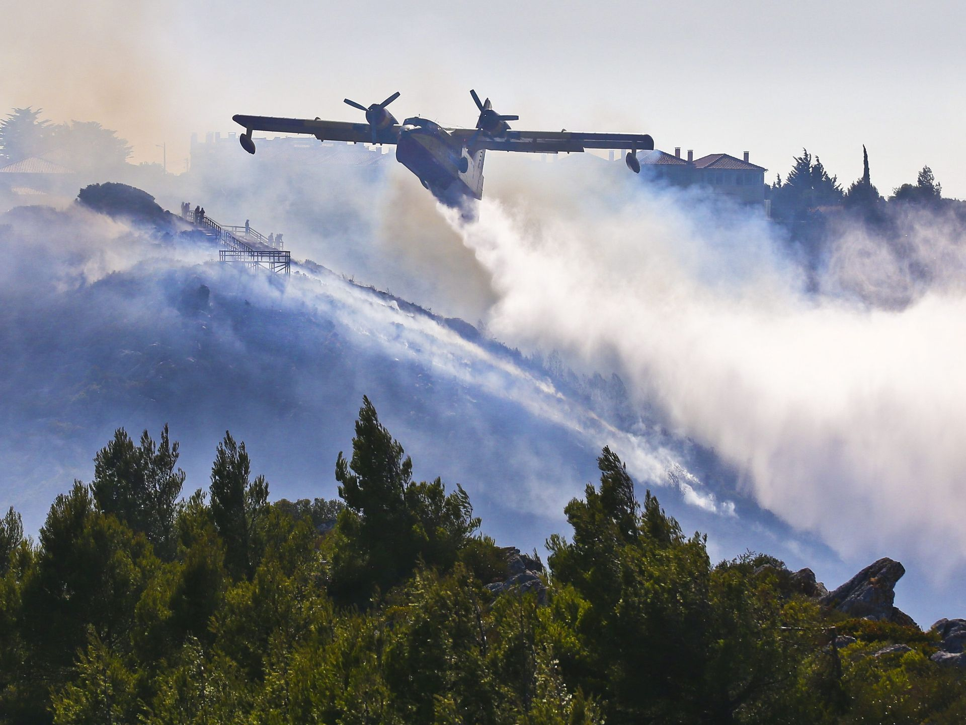 An airplane sprays water over a wildfire in Cascais, near Lisbon, Portugal.   Mario Cruz, European PressPhoto Agency
