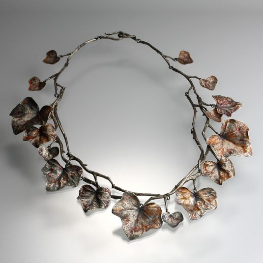 An antiqued sterling silver necklace with ivy leaves in various