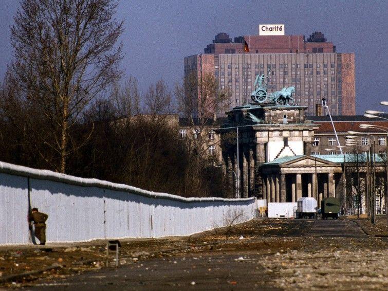 Ein Grenzsoldat schaut nahe dem Brandenburger Tor durch die Berliner Mauer nach West-Berlin (imago/NBL Bildarchiv)