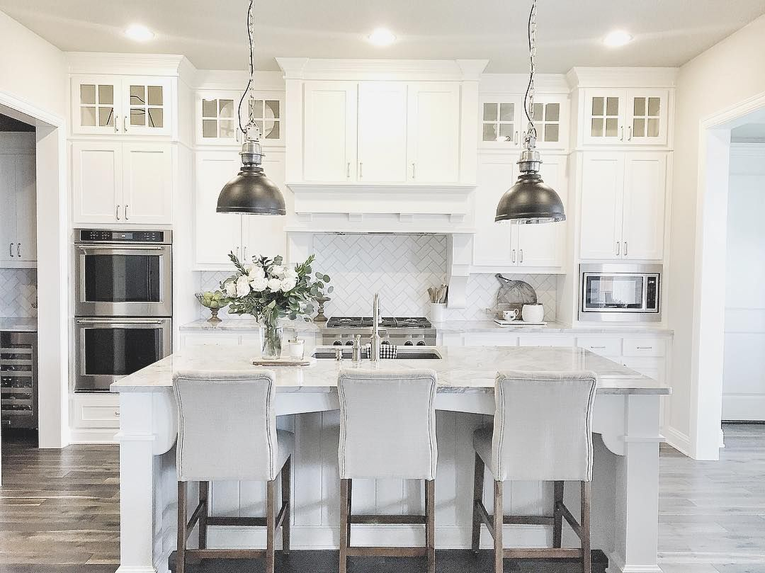 Gray and white kitchen with metal pendant lamps over large marble island