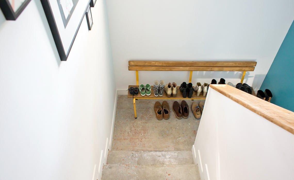 Un vieux banc d'école fait office de rangement des chaussures dans l'escalier.