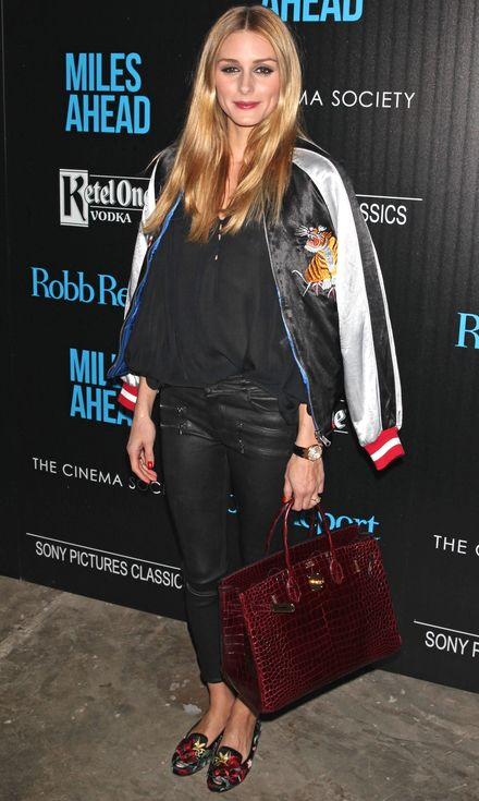 Olivia Palermo in a black top, leather pants, bomber jacket, printed flats and a red croc bag