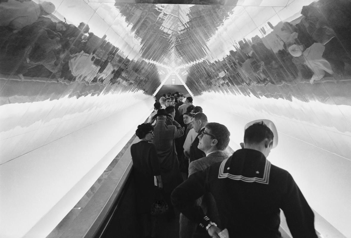 Riders on a moving walkway are reflected in the ceiling at the GE exhibit at the New York World's Fair, May 21, 1964.