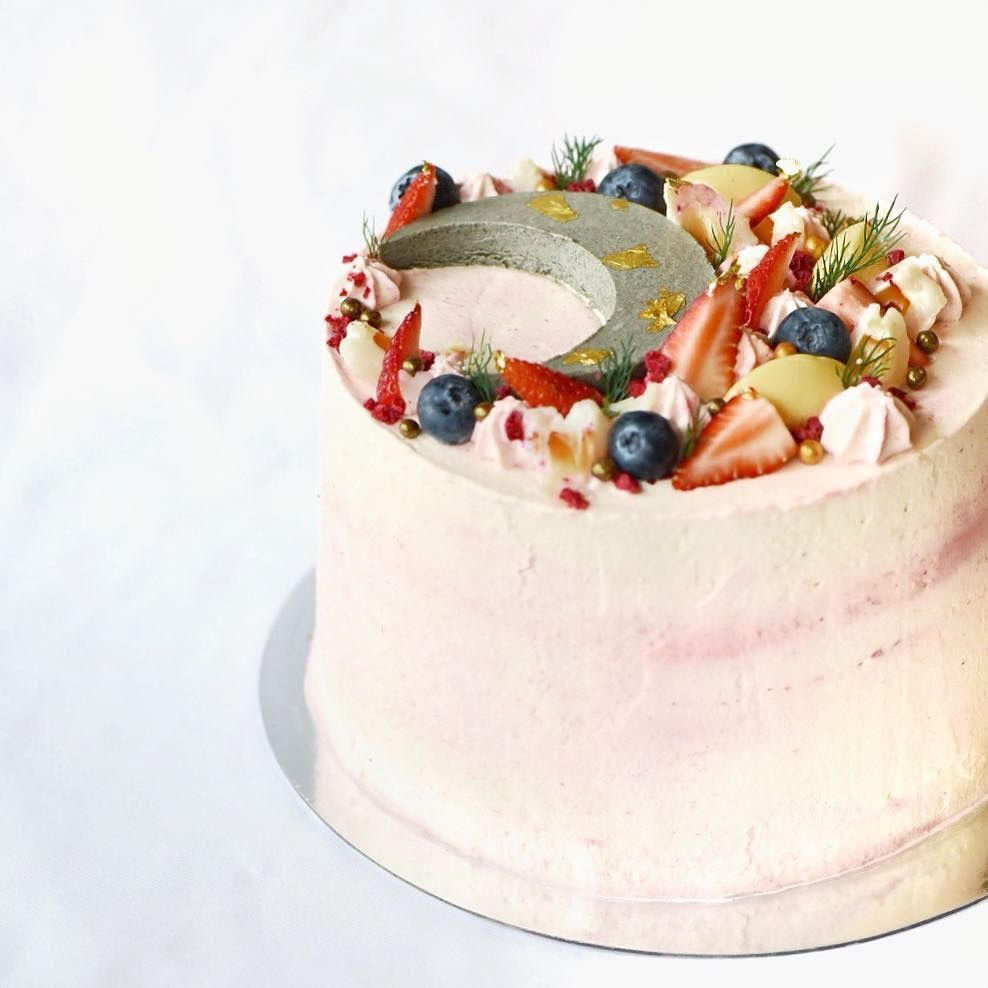 Raspberry Lychee & Rose cloud cake garnished with fruits & black ...