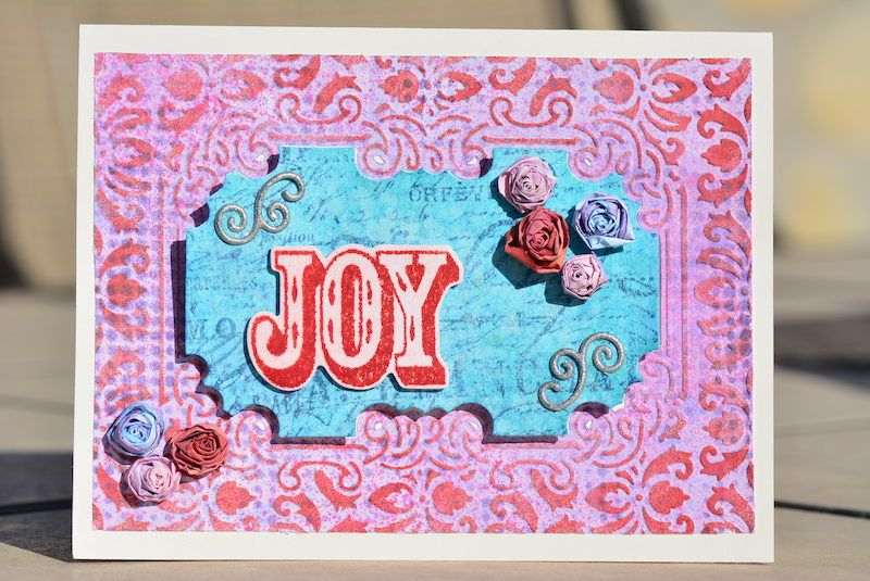 DIY card made from cuttlebug Embossing Plus folder (used to die cut, emboss, & stencil all in one).  Tutorial on handmade paper rosettes.  Also uses Tim Holtz Christmas framelit die/stamp & layering stencil.