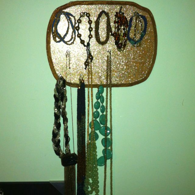 Easy jewelry holder.  Just a wood plaque from Michael's, painted with A LOT of layers of Martha Stewart brand multi-surface smoky quartz paint and nails for the hooks. Made it myself:)