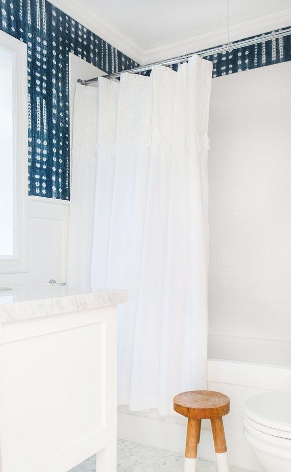 Blue and white wallpaper in white bathroom