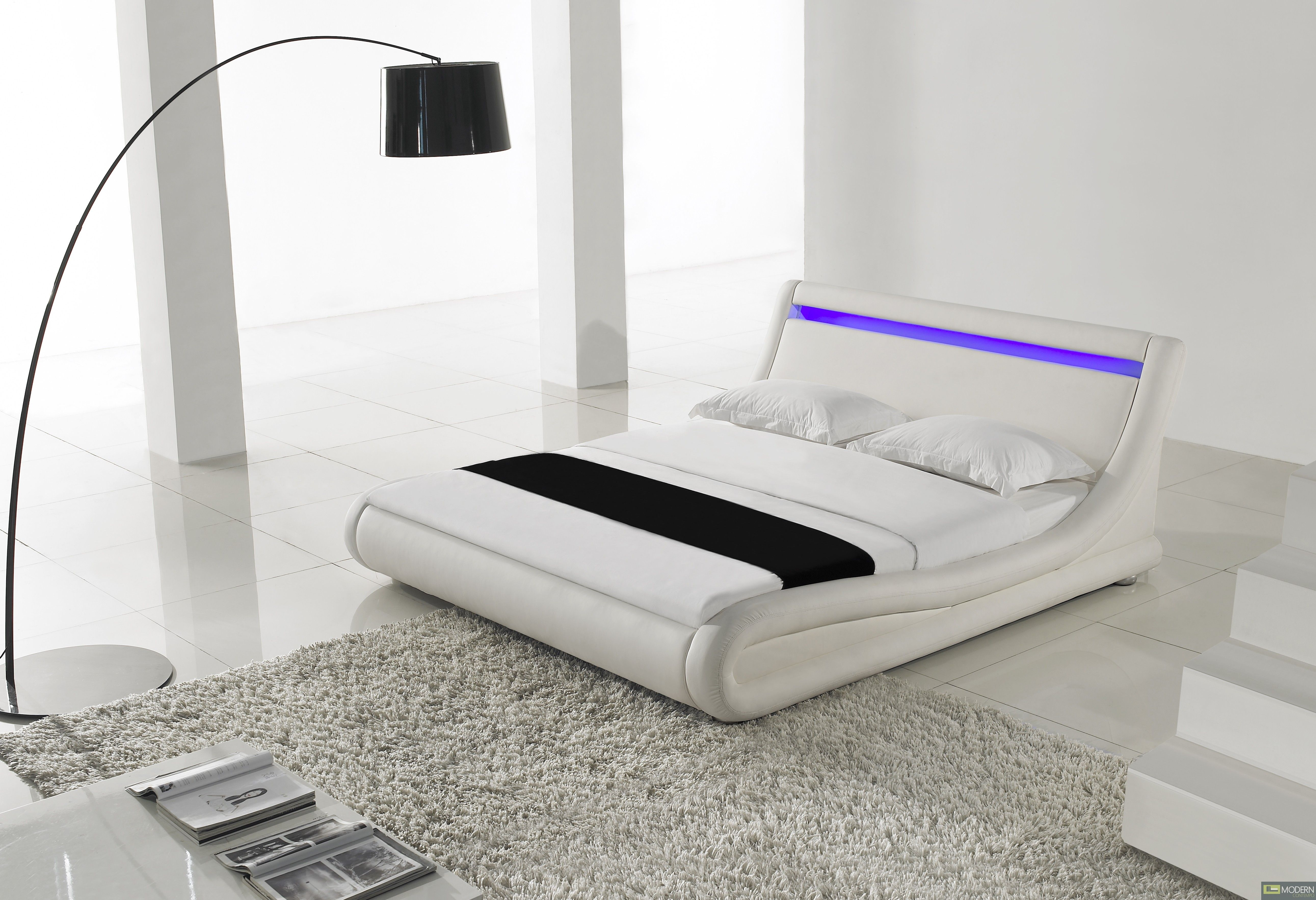Modern white platform bed with bright blue LED accent