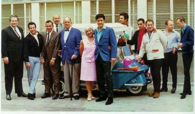 Courtesy of Larry Geller - Left to right: Ray Sitton, Joe Esposito, (unknown), Bullets Durgam, Colonel Tom Parker, Mrs. Marie Parker, Elvis, Larry Geller, George Klein, Alan Fortas, Marty Lacker, Richard Davis – in front of the Colonel's office at MGM Studios.