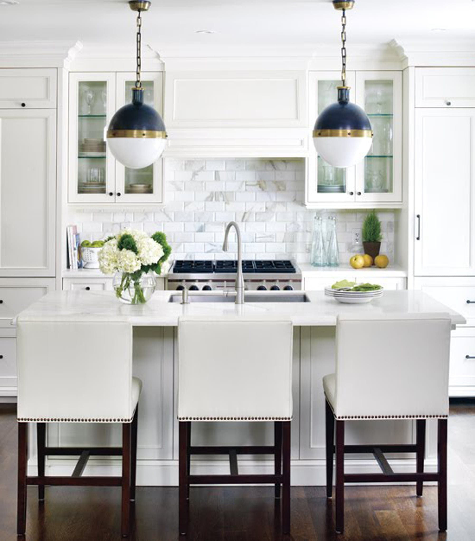 Soft white kitchen with marble subway tile backsplash cabinets topped with crown molding a custom panel to cover range hood nailhead trim counter stools