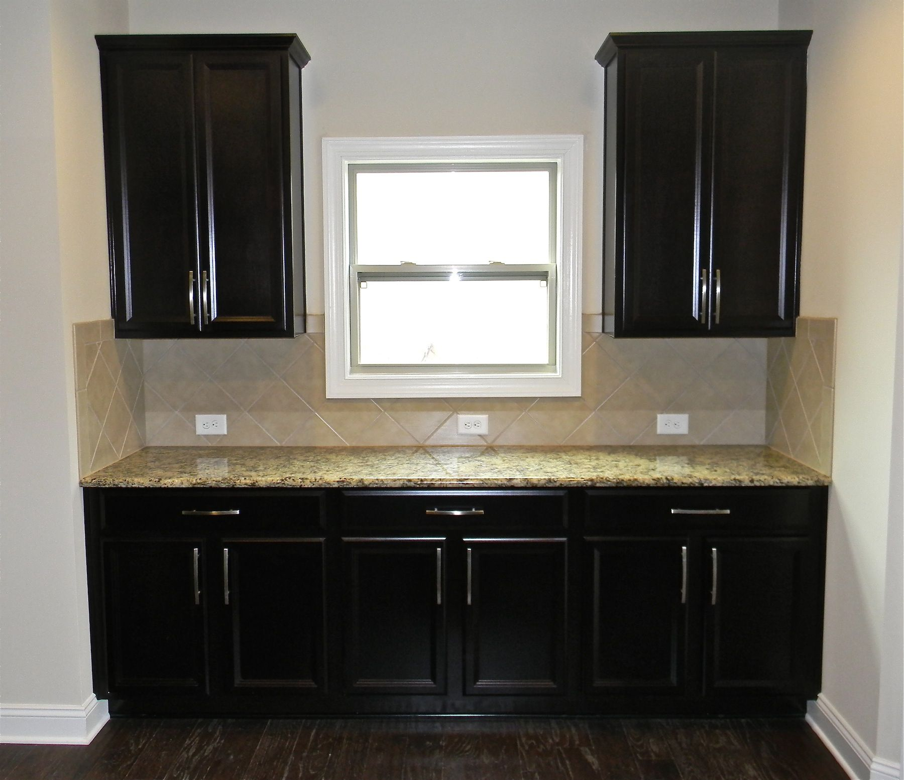 beautiful kitchen, dark custom cabinets, tumbled marble backsplash
