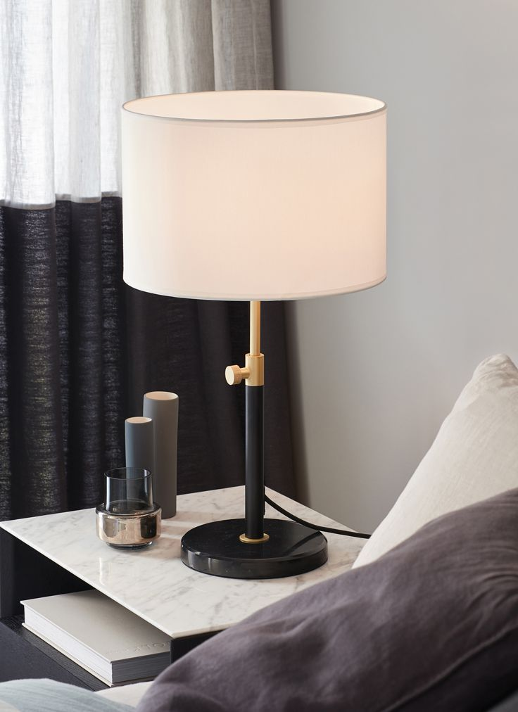 The beacon lighting albus 1 light table lamp with matte black base and brass detail with