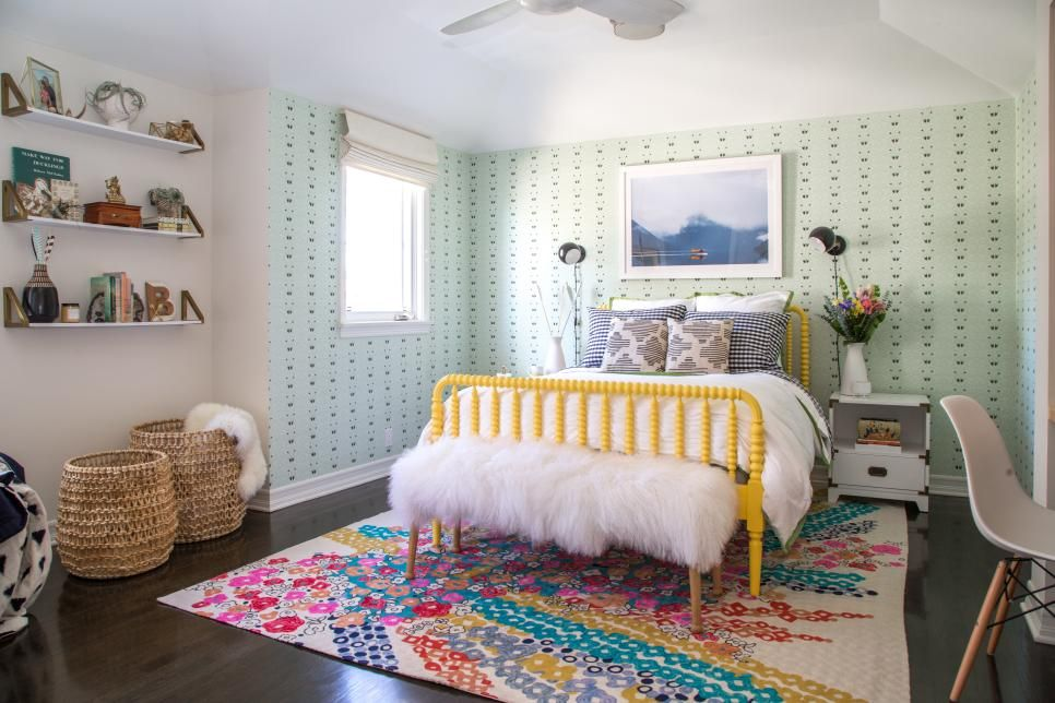 arrow themed wallpaper lends a graphic element to the tween bedroom where a bright yellow bed takes center stage adding a punch of color to the space