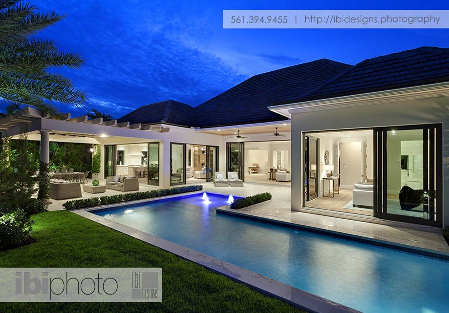 A modern L shaped pool with illuminated water features at ...