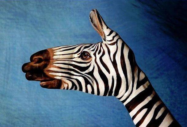 Body art sur une main transformée en tête de zèbre.