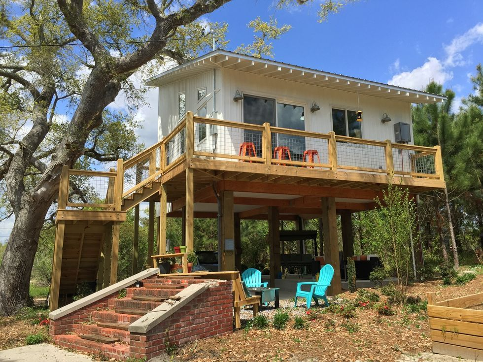 After Hurricane Katrina Washed Away Everything This Family Rebuilt Their House As A Tiny Cottage In 2020 Beach House Design House On Stilts Contemporary Beach House