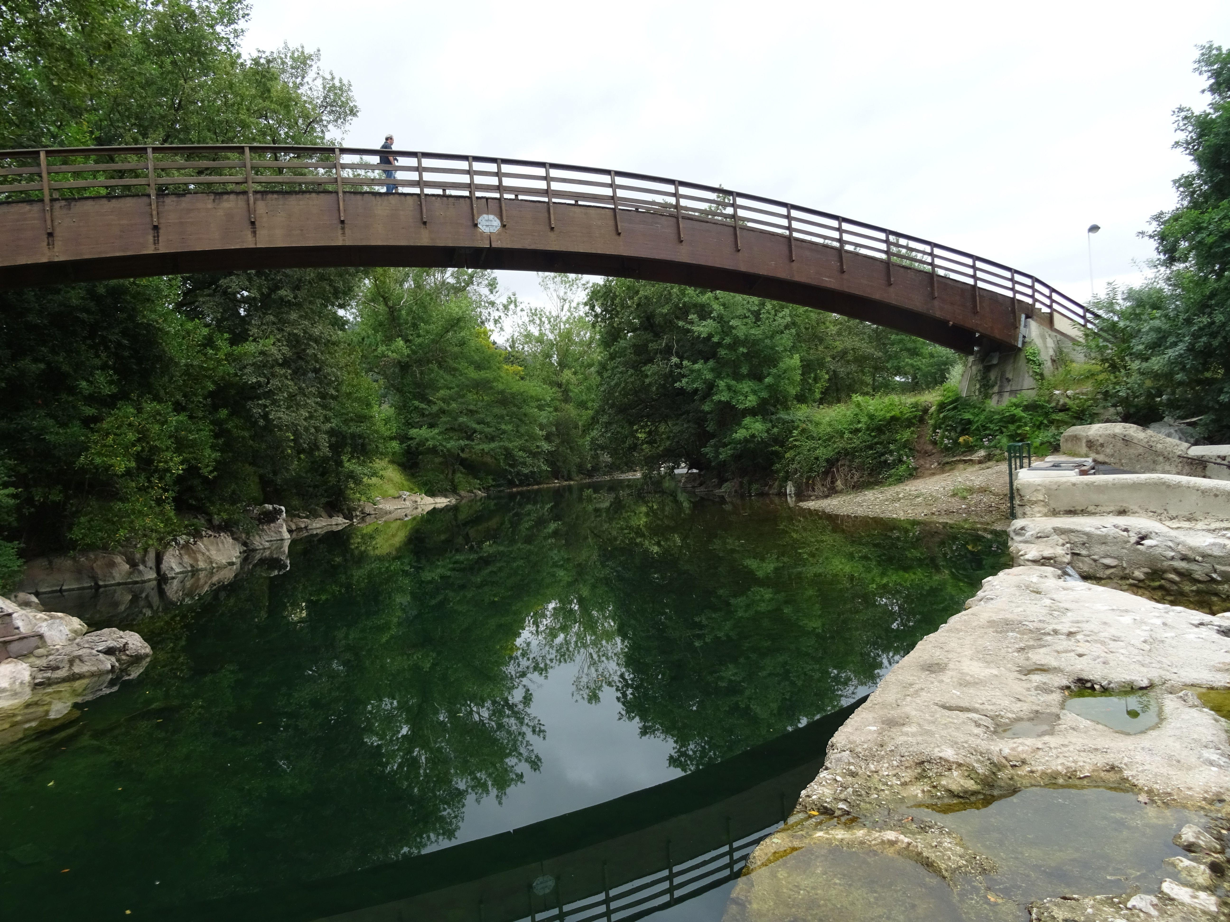 Puente sobre el río Pas, es un puente de hierro cuyo color rojizo destaca sobre el verde del paisaje y del río y el blanco de la roca
