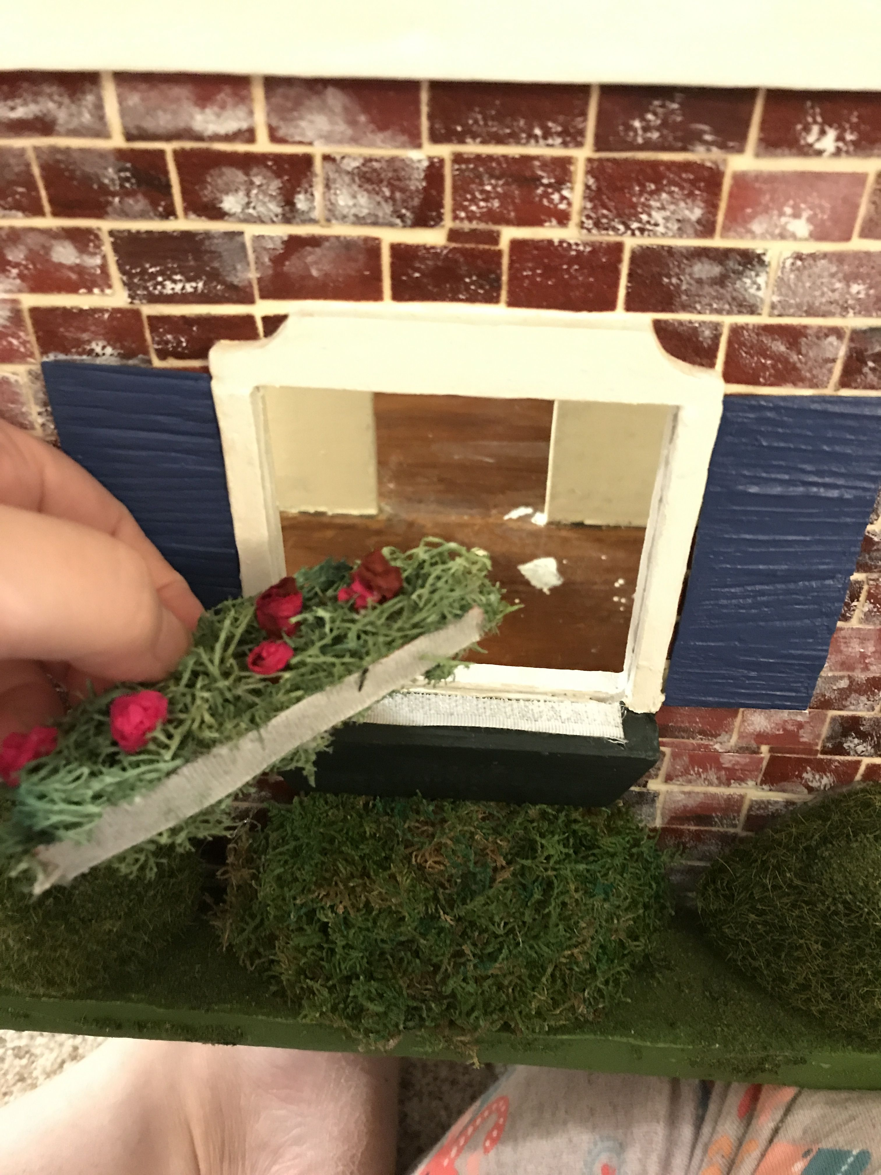 Create Velcro flower window boxes for your dollhouse to change them out seasonally. You need..hot glue gun..bag moss or loose greenery...strip of Velcro and plants of your choice.