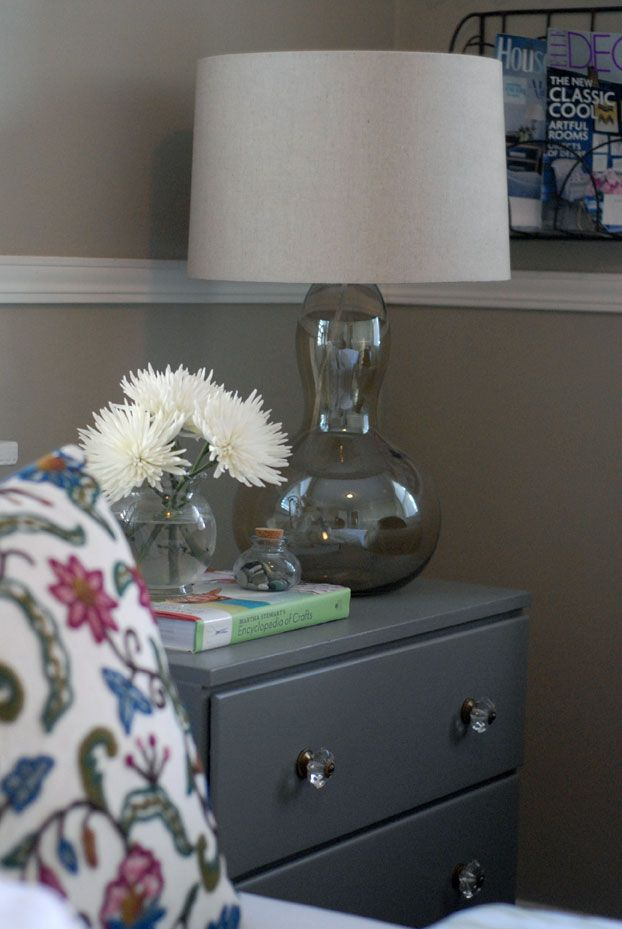 Guest Bedroom - small dresser as night table, with glass lamp and flowers.