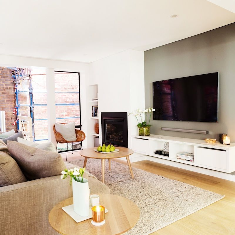 Living Room With Tv: Light Wooden Flooring, With White Cabinetry And A Feature