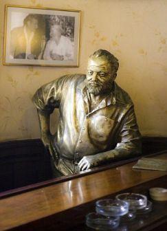 Ernest Hemingway statue in El Floridita bar, Havana, Cuba. Wall photo is of EH with Errol Flynn.