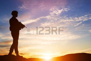 patriotic: Armed soldier with rifle standing and looking on horizon. Silhouette at sunset. War, army, military, guard Stock Photo