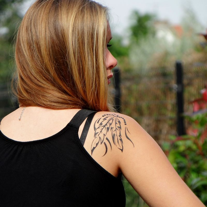tatouage temporaire plumes d'indien sur l'arrière de l'épaule