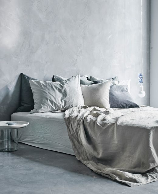 A Large Bed, Low To The Floor Covered In Light Gray Textiles.