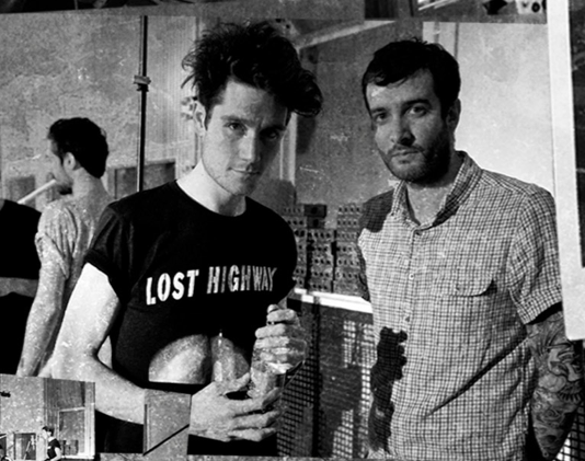 Dan Smith of Bastille, making a face, in his Lost Highway shirt, with messy hair, holding a water bottle