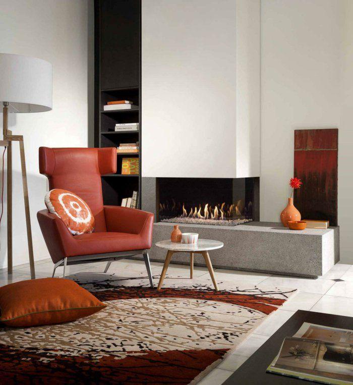 Feuerstelle Wohnzimmer Warme Farben Teppich Oranger Sessel Weiße Wände