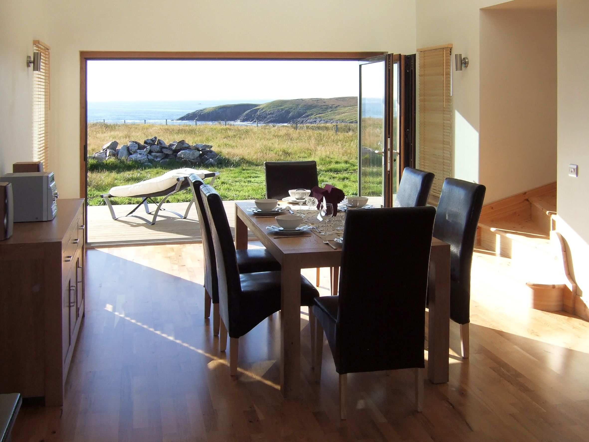 photo of sunfold dining room with folding sliding doors sliding doors and sea view & Amazing views from this composite 3 panel set of bi folding doors ...