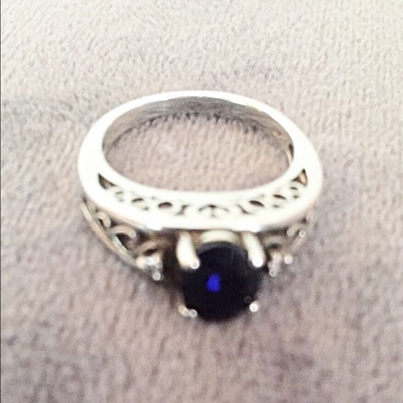 Blue Gemstone & Sterling Silver Ring Beautiful blue gemstone (not sure whether it is sapphire) in a dainty Sterling silver setting. Band width is 5 mm. 925 Sterling silver. Jewelry Rings