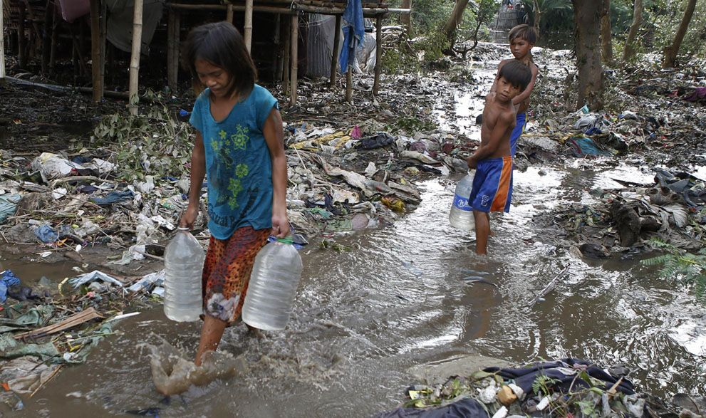 Residents carry plastic containers of potable water as they wade through debris and mud brought by Typhoon Rammasun in a coastal village of ...