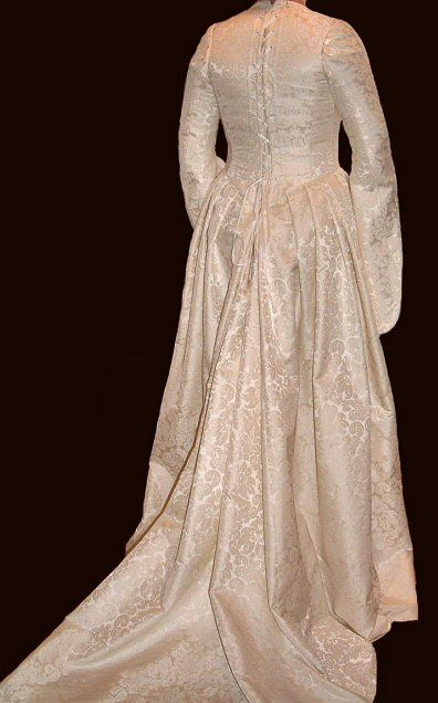 Ivory silk damask, with gold lace and beadwork embellishing the ...