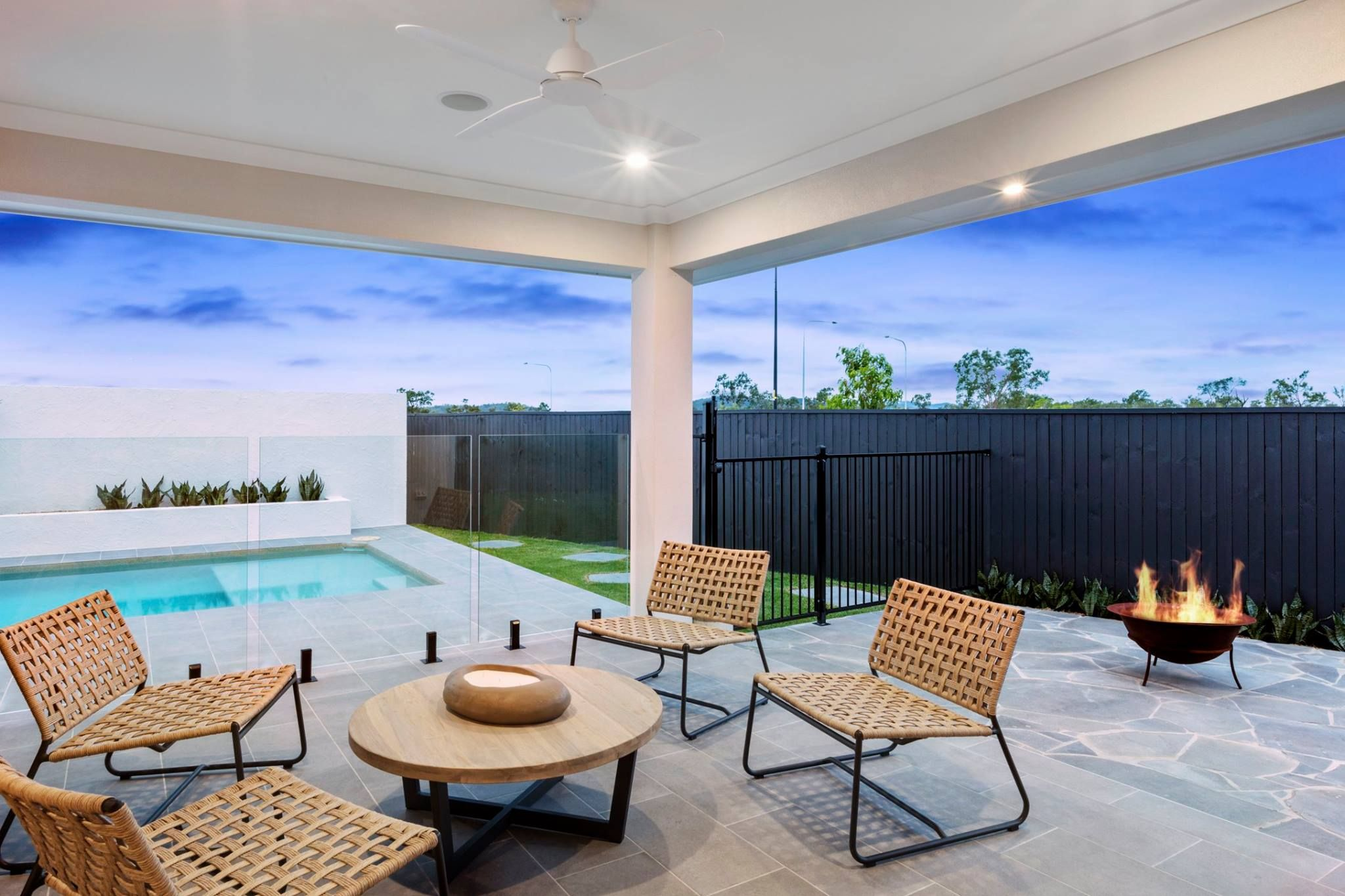 You'll be spending all your time outside with this G.J. Gardner Homes outside alfresco. With space to sit and relax, as well as the sleek look of a glass gated pool, this  backyard has it all.