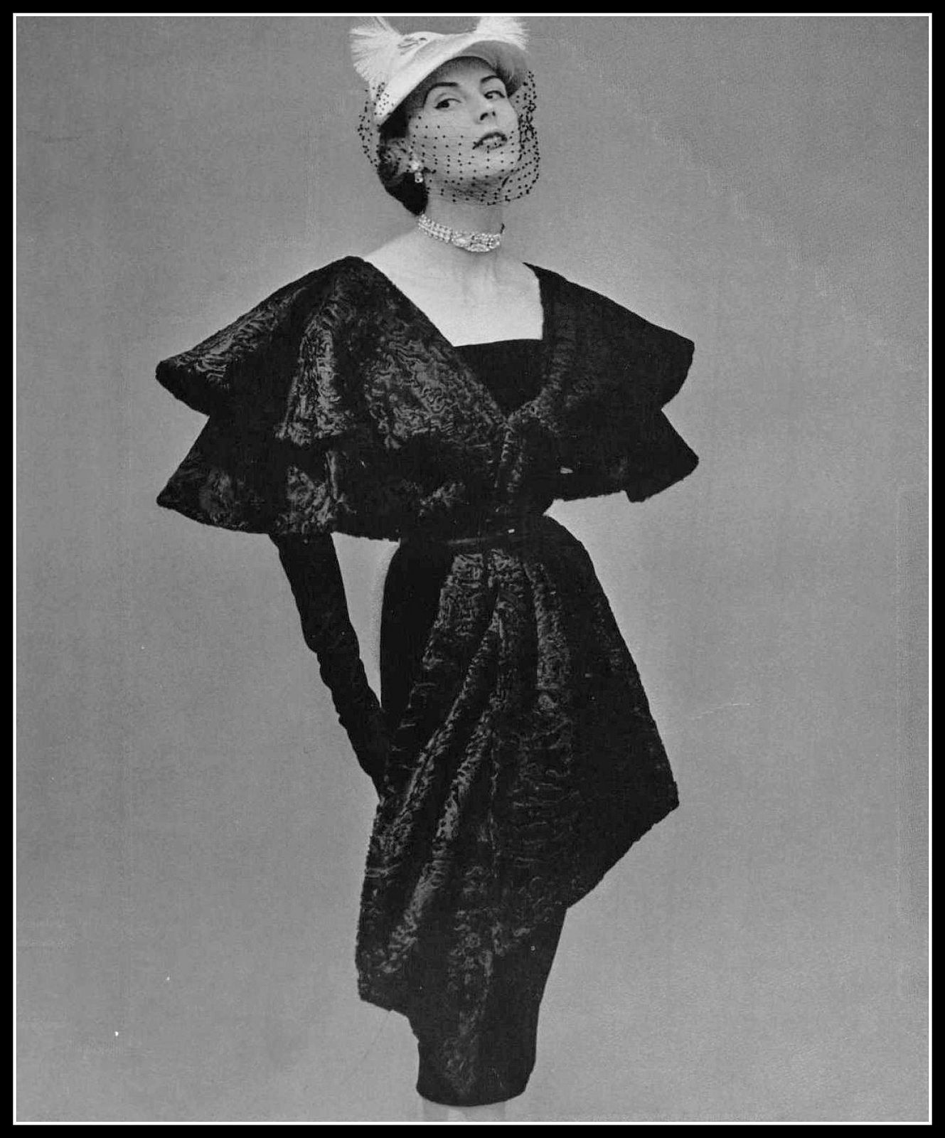 Model in elongated astrakhan cape-stole over black velvet sheath by Jacques Fath, jewelry by Roger Scémama, photo by Pottier, 1951