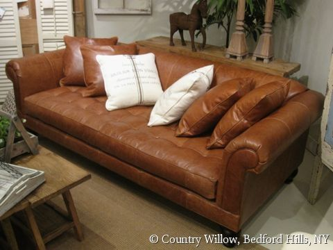 brown single-cushion leather sofa with toss pillows and ...