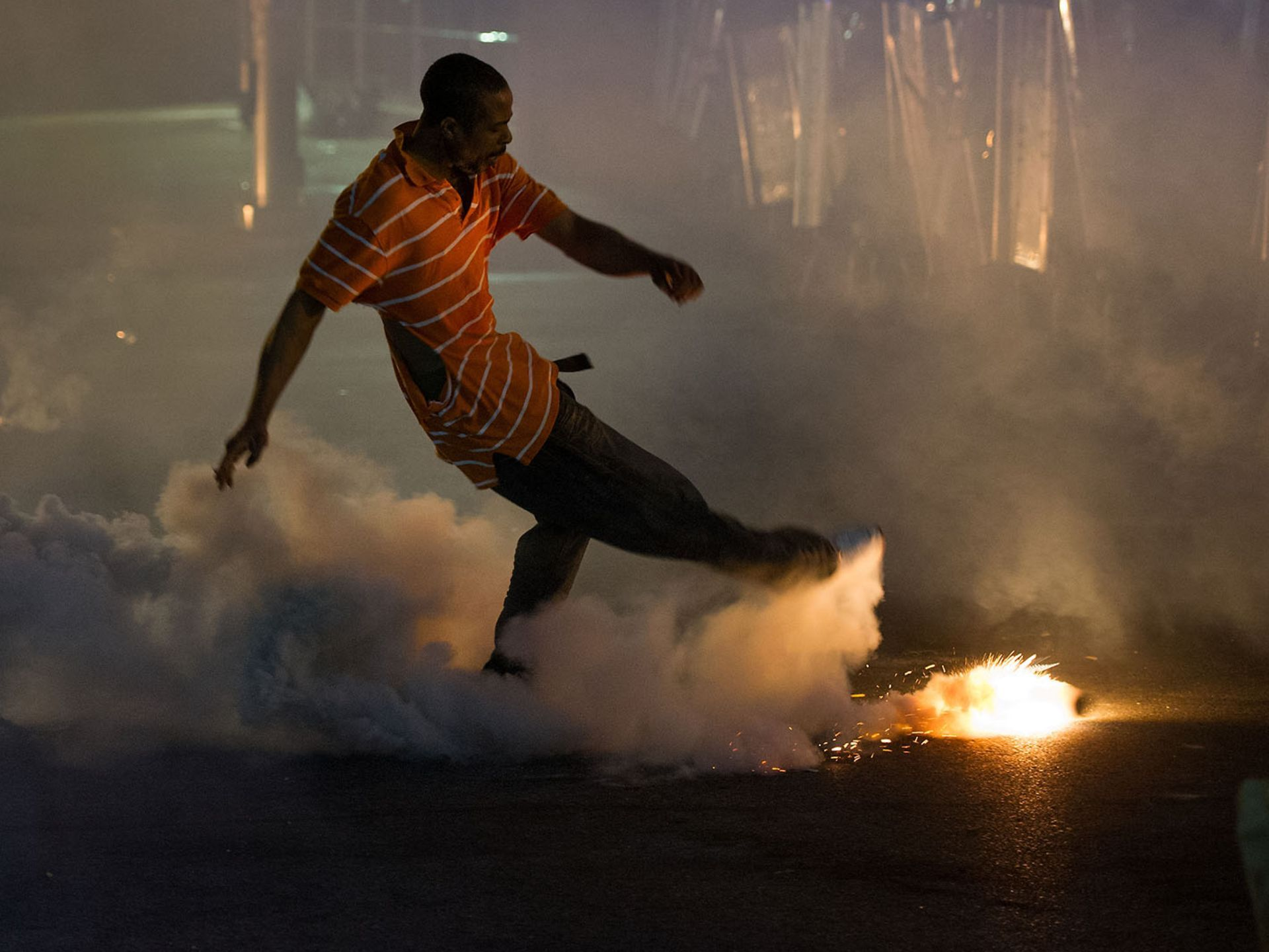 A protester kicks away a tear gas canister as police advance on demonstrators after a 10 p.m. curfew began on April 28 on North Avenue in Baltimore. Police attempted to restore order after violence rocked the city following the funeral for Freddie Gray, who died while in police custody.  Jack Gruber, USA TODAY