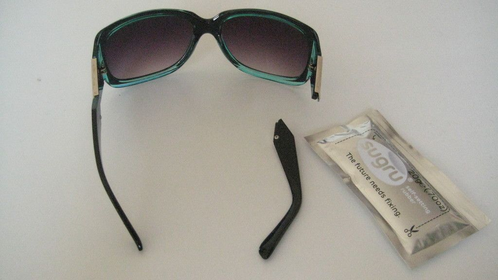 Broken glasses with snapped arm next to packet of Sugru