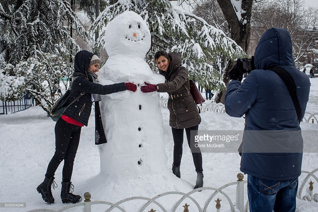 People Pose For A Photograph With A Snowman Outside The