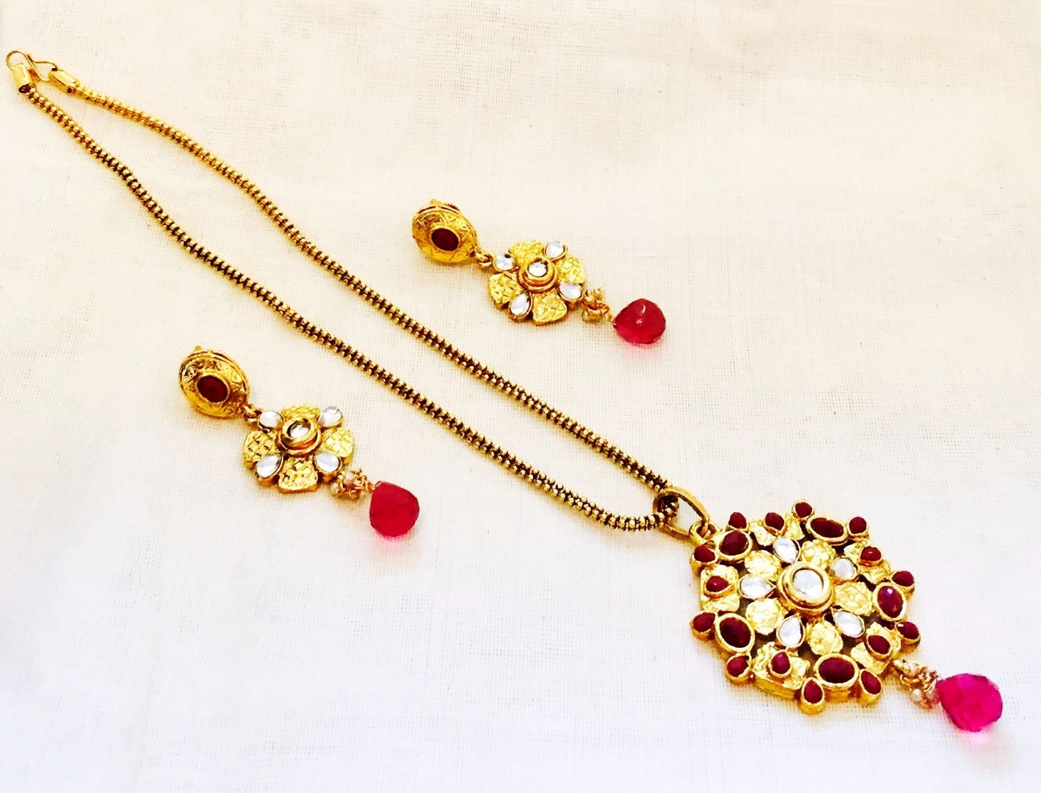 Antique gold coated polki pendant jewellery set with red accent