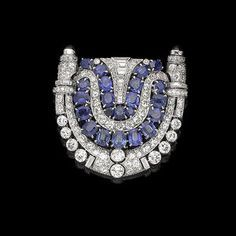 An art deco sapphire and diamond brooch, circa 1930 The openwork shield-shaped plaque of geometric design, composed of two rows of cushion-shaped and circular-cut sapphires, within a surround of baguette, old brilliant, rose, single-cut and trapezoid-shaped diamonds, highlighted with circular cabochon sapphire terminals, the gallery decorated with engraved Greek key pattern, diamonds approx. 5.10cts total, partially struck maker's mark, French assay marks, length 4.4cm