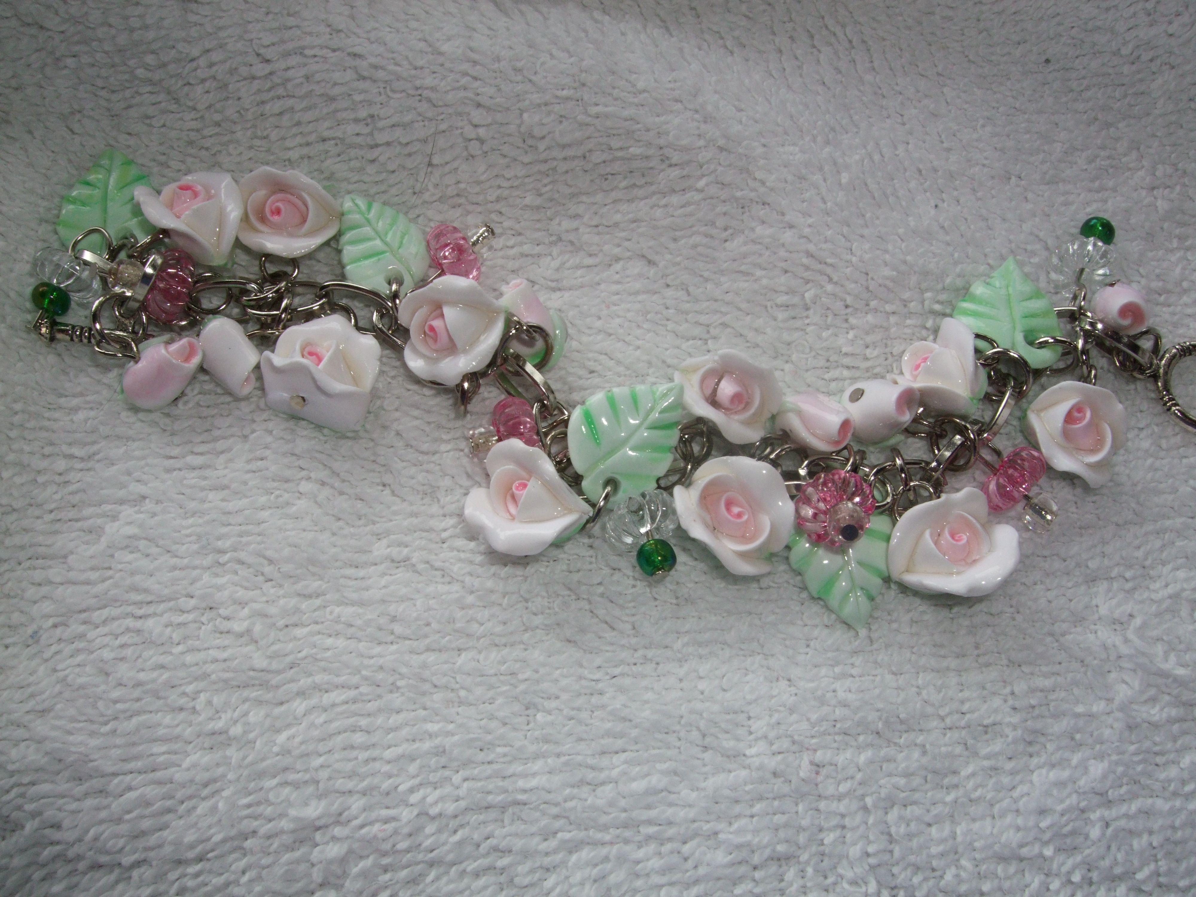 Pink rosebud, bead and green leaf charm bracelet.   #handmade #CreatingCottage #Roses #CottageStyle #Cottage #ShabbyChic #Shabby #Chic #polymerclay #white #pink #romantic  @Renee Holtzer